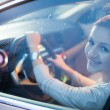 Pretty young woman driving her brand new car — Stock fotografie