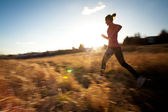 Young woman running outdoors on a lovely sunny winter/fall day — Stock Photo
