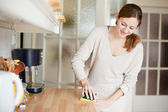 Young woman doing housework, cleaning the kitchen — Stock Photo