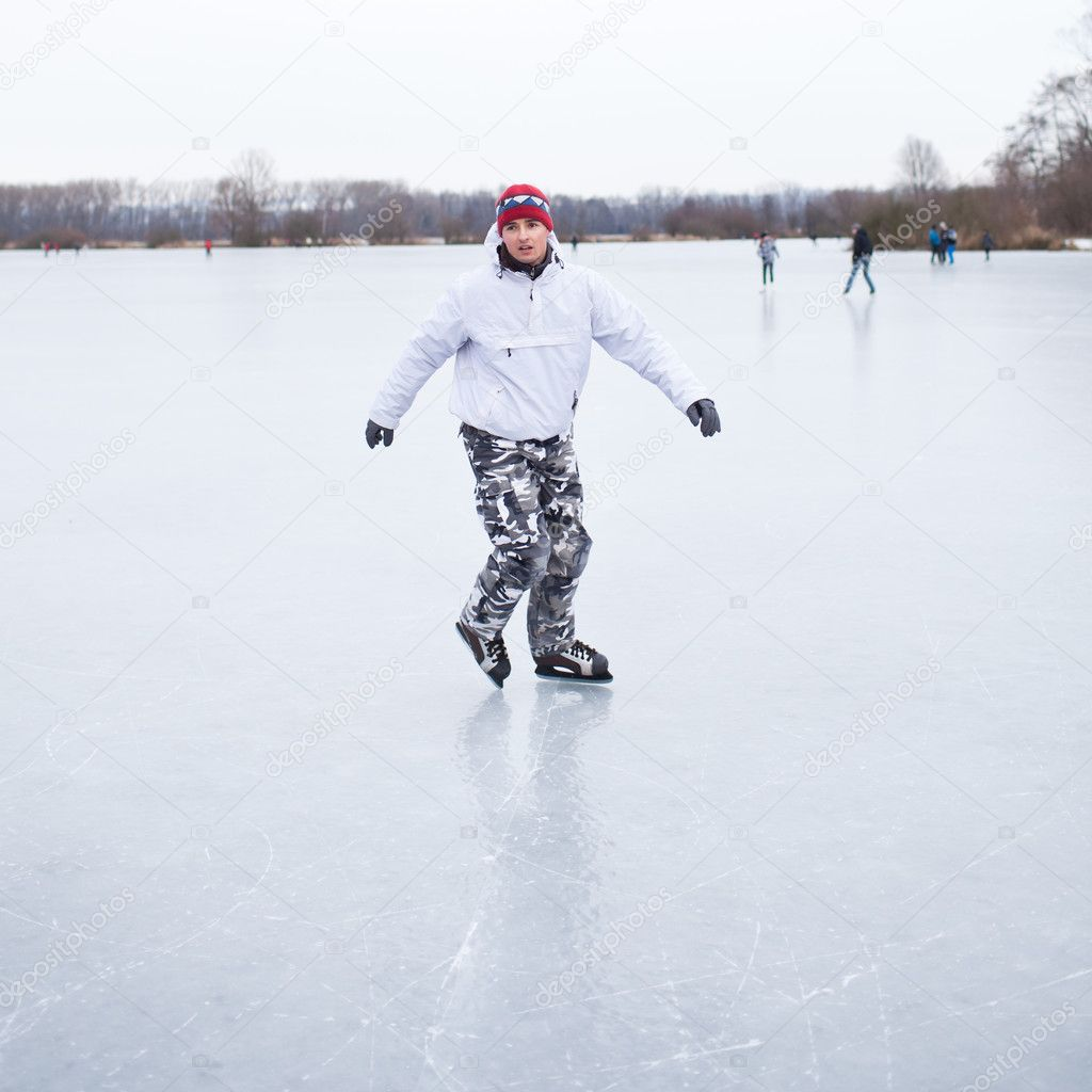 Handsome young man ice skating outdoors on a pond on a cloudy winter day (color toned image; shallow DOF) — Stock Photo #9115165
