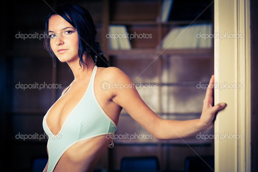 Alluring brunette wearing swimsuit and standing in an office — Stock Photo #9115326