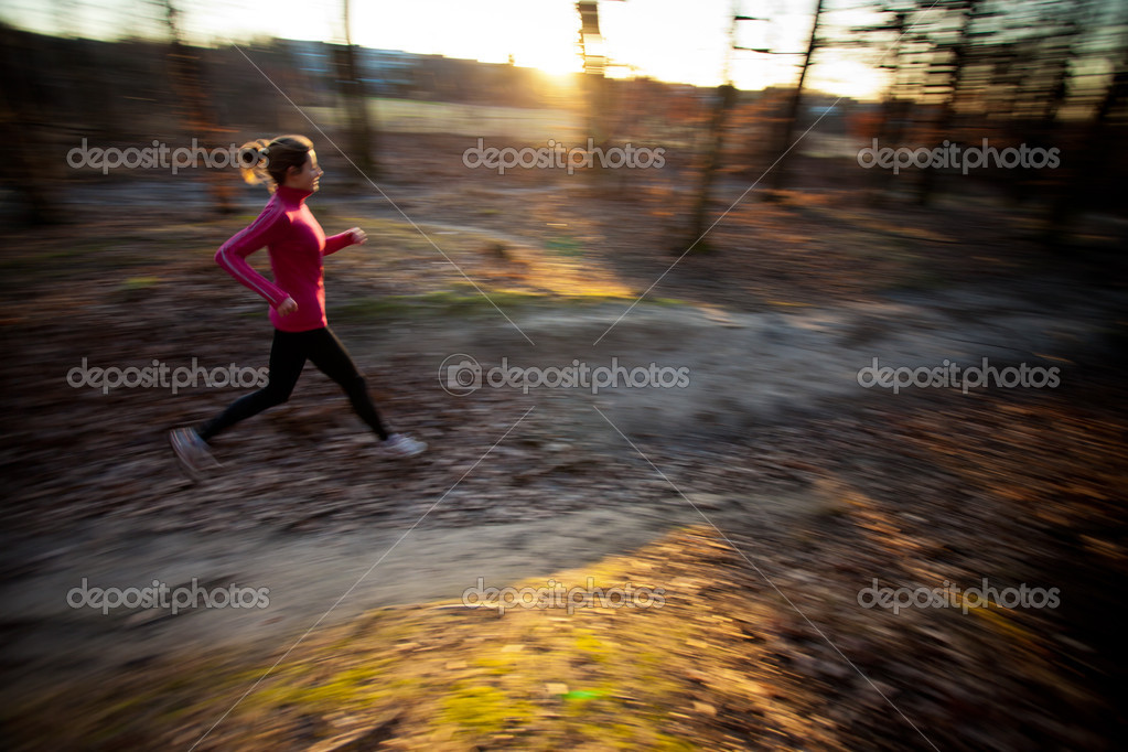 Young woman running outdoors in a city park on a cold fall/winter day (motion blurred image) — Stock Photo #9115452