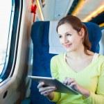 Jeune femme à l'aide de son ordinateur tablette lors d'un voyage en train — Photo