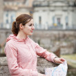 Pretty young female tourist holding a map in Rome - Stockfoto