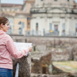Pretty young female tourist holding a map in Rome - Foto de Stock
