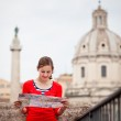Pretty young female tourist holding a map in Rome — Stock Photo #9269768