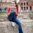 Pretty young female tourist holding a map in Rome — Stock Photo #9269776