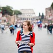 Pretty young female tourist holding a map in Rome — Stock Photo #9269782