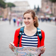 Stock Photo: Pretty young female tourist holding a map in Rome