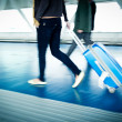 With their suitcases walking along a corridor - Stock Photo