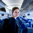 Pretty young female passenger on board of an aircraft - Stockfoto