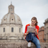 Pretty young female tourist holding a map in Rome — Stock Photo