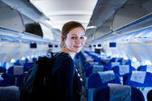 Pretty young female passenger on board of an aircraft — Stock Photo