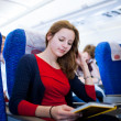 Pretty young female passenger on board of an aircraft - Stock Photo