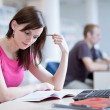 Stock Photo: Pretty female student in the library
