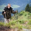 Active senior hiking in high mountains (Swiss Alps) - Stock Photo