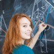 Pretty young college student writing on the blackboard - Stock Photo