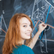 Pretty young college student writing on the blackboard — Stock Photo