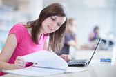Pretty female student in the library — Foto de Stock