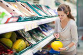 Pretty, young woman shopping for fruits and vegetables — Stock Photo