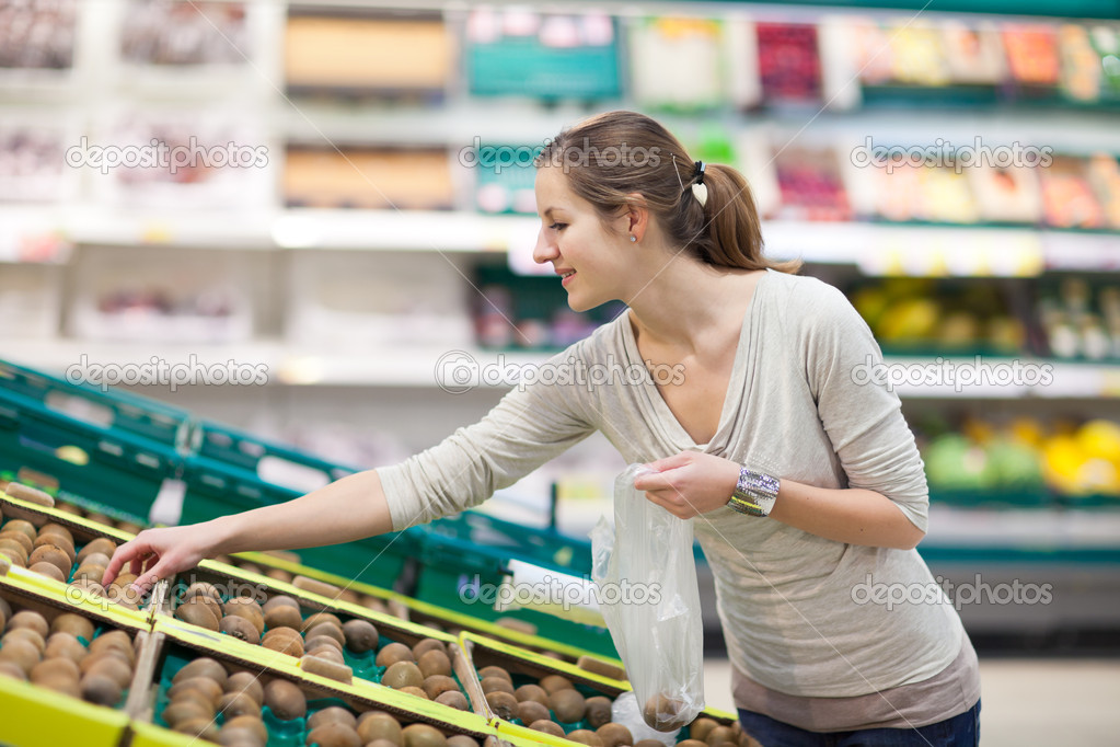 Beautiful youn woman shopping for fruits and vegetables in produce department of a grocery store/supermarket (shallow DOF; color toned image) — Stock Photo #9388919