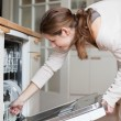 Stock Photo: Young woman using a dishwasher