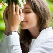 Beautiful young woman smelling white jasmin flowers — Stock Photo #9557344