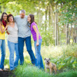 Family portrait - Family of four with a cute dog outdoors - Stock Photo