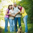 Family portrait - Family of four with a cute dog outdoors — Stock Photo #9557387