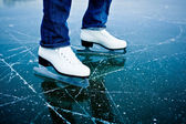 Young woman ice skating outdoors on a pond — Stok fotoğraf