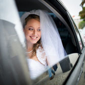Portrait of a beautiful young bride waiting in the car — Stock Photo