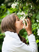 Beautiful young woman smelling white jasmin flowers — Stock Photo