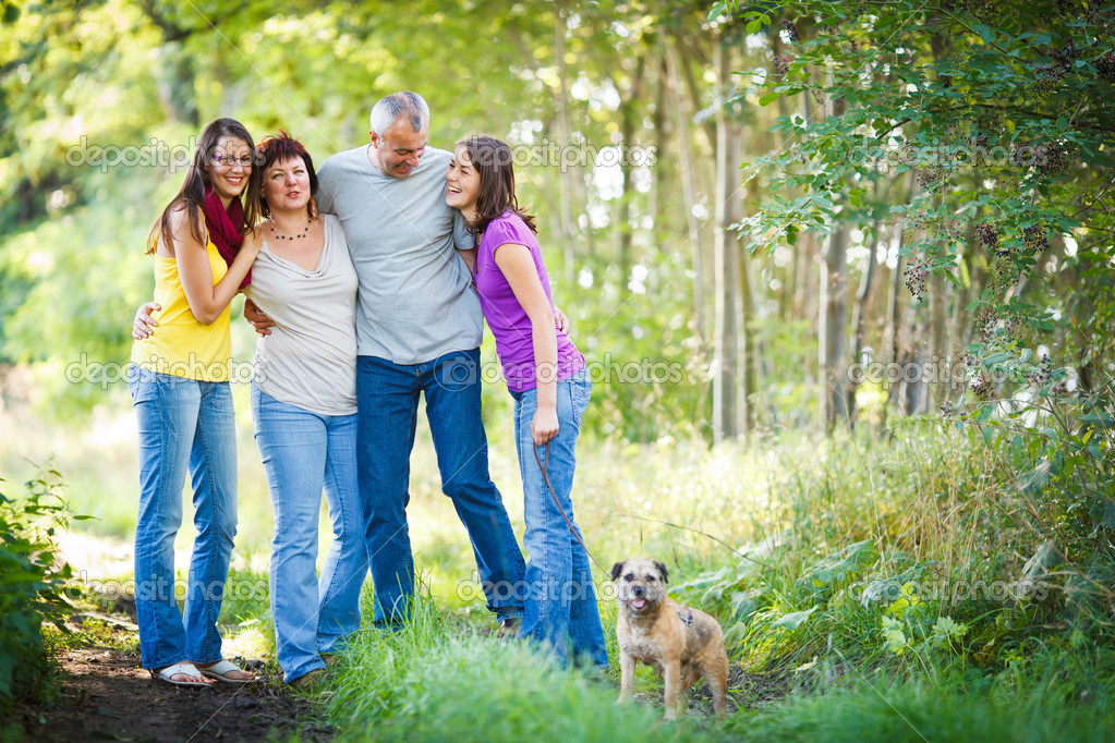 Family portrait - Family of four with a cute dog outdoors — Stock Photo #9557373