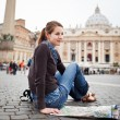Pretty young female tourist studying a map at St. Peter's square — Stock Photo #9790226