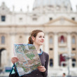 Pretty young female tourist studying a map at St. Peter's square — Stock Photo #9790259