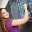 Pretty young college student writing on the chalkboard/blackboar - Stock Photo