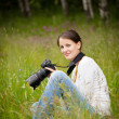 Pretty young woman with a DSLR camera outdoors, taking pictures — Stock Photo