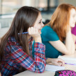 Young pretty female college student sitting in a classroom full — Stock Photo