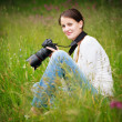 Pretty young woman with a DSLR camera outdoors, taking pictures — Stock Photo #9790372