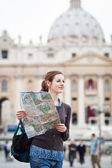 Pretty young female tourist studying a map at St. Peter's square — Stockfoto