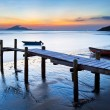Sunset at wooden pier along the coast — Stock Photo