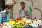 Chinese hawker selling fruits — Stock Photo