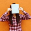Asian woman using book to cover face — Stock Photo #8921262