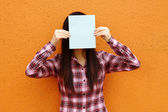 Asian woman using book to cover face — Stock Photo