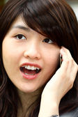 Young asian woman talking on phone — Stock Photo