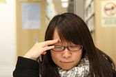 Asian woman thinking and studying in library — Stok fotoğraf