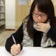 Asian woman studying in library — Stock Photo