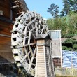 Water wheel next to a house - Stock Photo
