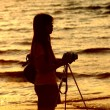 Female photographer under sunset — Stock Photo