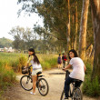 Asian friends riding bicycle — Stock Photo